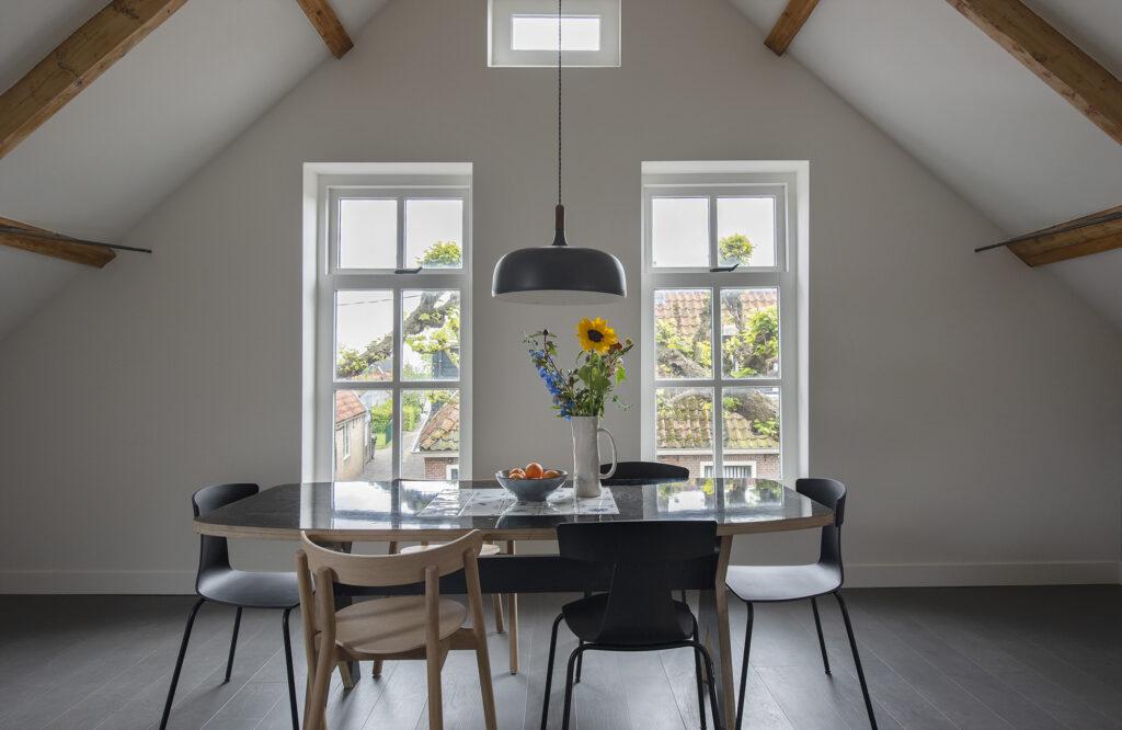 donkerblauwe tafel met stoelen voor het raam