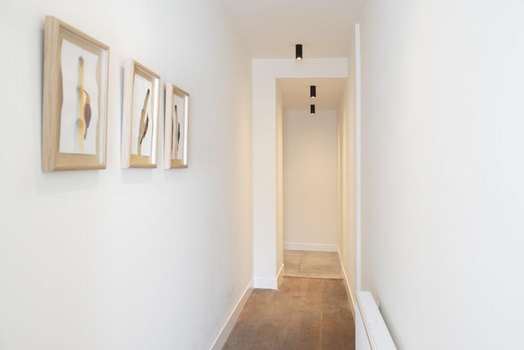 gang met houten vloer en witte wanden