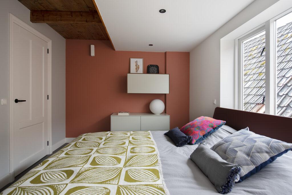 slaapkamer met steenrode wand, bed met spre en kussens van Claar & Co