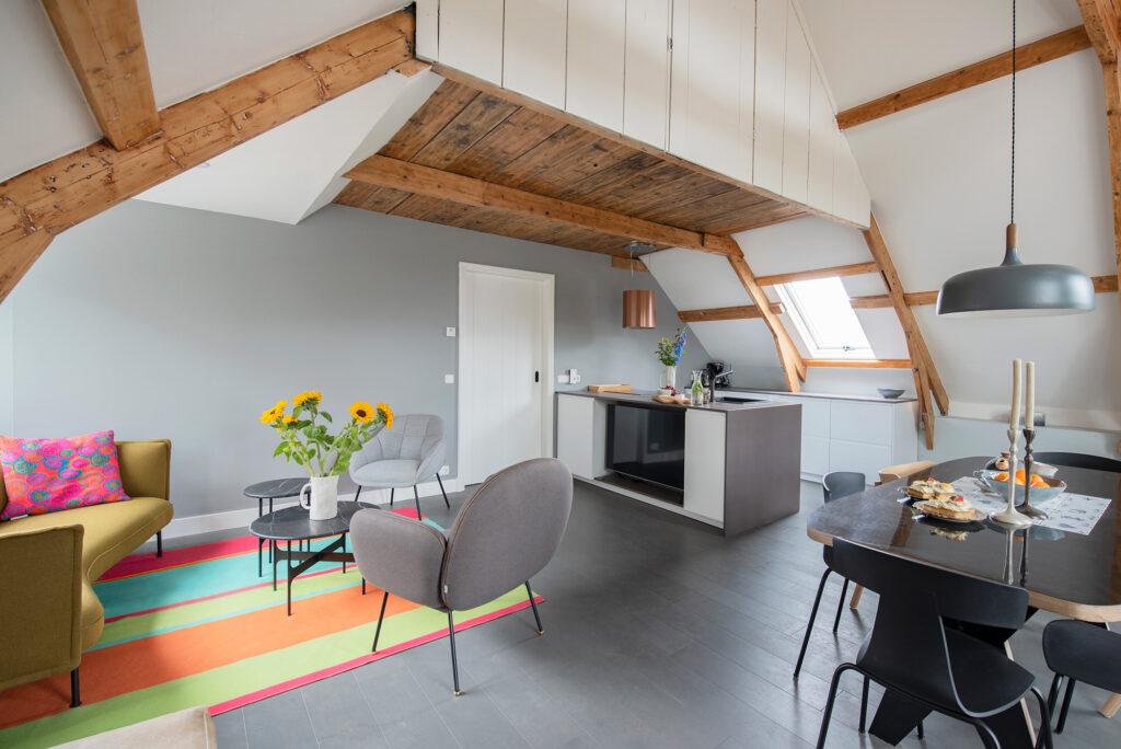 kamer met balkenplafond, witte keuken, gestreept vloerkleed, grijze fauteuil, zonnebloemen