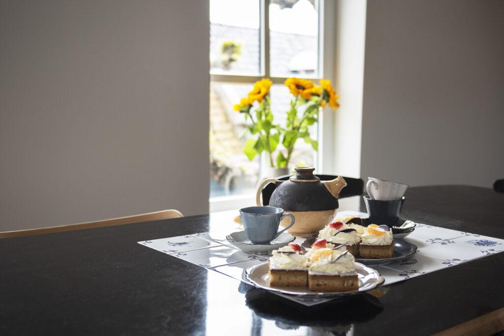 donkerblauwe tafel met tegeltableau, theeservies en oranjekoek