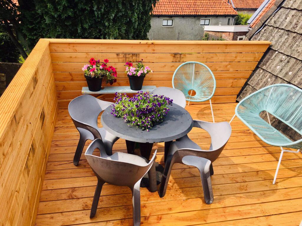 balkon, houten vlonder, grijze stoelen en tafel